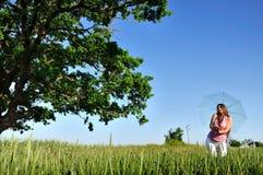 Giovane donna in un campo con l'ombrello Fotografia Stock