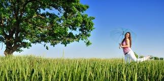Giovane donna in un campo con l'ombrello panoramico Fotografia Stock