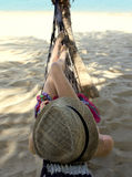 Giovane donna in un cappello di paglia d'uso dell'amaca Immagine Stock Libera da Diritti