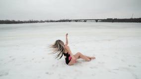 Giovane donna in un costume da bagno che posa nella neve video d archivio