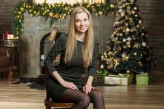 Giovane donna in un interno accogliente del Natale La ragazza si siede sotto un albero di Natale fra molti regali Preparando per  Immagine Stock