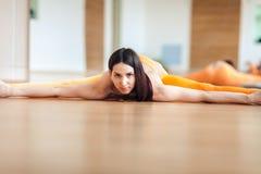Giovane donna in un vestito di sport che fa allungamento, sedentesi su una corda Riscaldamento prima di yoga Fotografie Stock