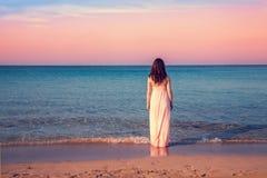 Giovane donna in un vestito lungo sulla spiaggia immagini stock libere da diritti