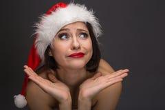 Giovane donna in una gonna ed in un cappello rossi del Babbo Natale su un backgr leggero Fotografie Stock Libere da Diritti