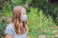 Giovane donna in una maschera medica a causa di un'allergia all'ambrosia Immagine Stock Libera da Diritti