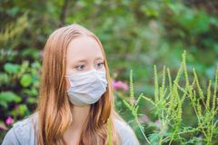Giovane donna in una maschera medica a causa di un'allergia all'ambrosia Fotografia Stock
