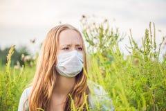 Giovane donna in una maschera medica a causa di un'allergia all'ambrosia Fotografie Stock