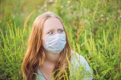Giovane donna in una maschera medica a causa di un'allergia all'ambrosia Fotografie Stock Libere da Diritti