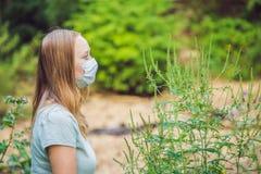 Giovane donna in una maschera medica a causa di un'allergia all'ambrosia Immagini Stock