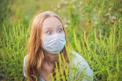Giovane donna in una maschera medica a causa di un'allergia all'ambrosia Fotografia Stock Libera da Diritti