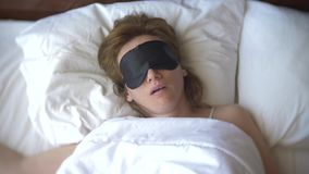 Giovane donna in una maschera per il sonno, addormentata a letto su un cuscino di giorno fotografia stock