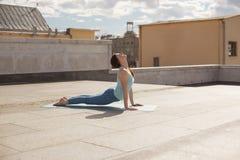 Giovane donna in una posa ascendente del cane del rivestimento di yoga Fotografia Stock