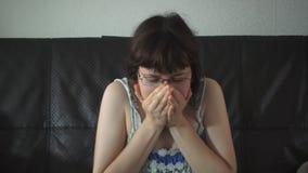 Giovane donna in una seduta di starnuto della camicia da notte a casa su un'agrostide volgare archivi video