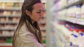Giovane donna in una sezione della latteria del supermercato che sceglie una bottiglia di latte video d archivio