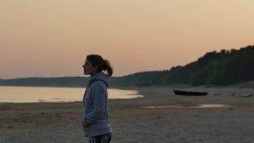 Giovane donna vaga che gode del sole sulla spiaggia Vista sul mare baltica nordica 4k UHD stock footage