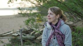Giovane donna vaga che gode del sole sulla spiaggia Vista sul mare baltica nordica 4k UHD video d archivio