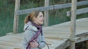 Giovane donna vaga che gode del sole vicino alla vista sul mare baltica nordica della foresta e del mare 4k UHD archivi video