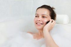 Giovane donna in vasca che parla sul cellulare immagini stock libere da diritti