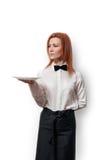 Giovane donna in vassoio della tenuta dell'uniforme del cameriere sopra fondo bianco fotografia stock libera da diritti