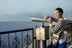 Giovane donna vera che esamina tramite il telescopio il mare Immagine Stock Libera da Diritti