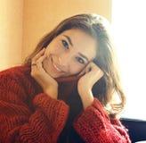 Giovane donna vera graziosa in maglione e sciarpa rossi da ogni parte del suo fa immagine stock libera da diritti