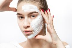 Giovane donna vestita in vestiti bianchi con una maschera cosmetica bianca fotografie stock libere da diritti