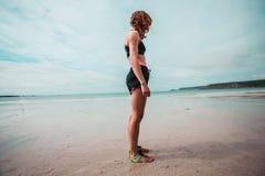 Giovane donna in vestiti di allenamento che stanno sulla spiaggia Immagine Stock Libera da Diritti