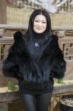 Giovane donna in vestiti di pelliccia scura Immagini Stock