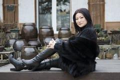 Giovane donna in vestiti di pelliccia scura che si siedono davanti alla casa coreana con i wases. Immagine Stock Libera da Diritti