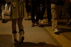 Giovane donna in vestiti di progettista che cammina da un gruppo di uomini alla notte immagine stock libera da diritti