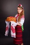 Giovane donna in vestiti ucraini, con la ghirlanda e la pagnotta rotonda immagine stock libera da diritti