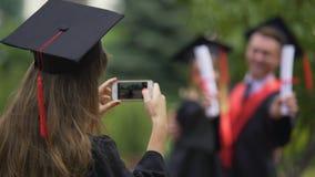 Giovane donna in vestito accademico che prende le foto degli amici sul cellulare, graduazione archivi video