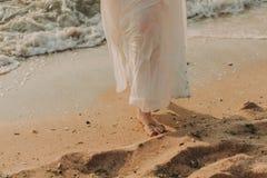 Giovane donna in vestito bianco che cammina sulla spiaggia immagine stock