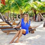 Giovane donna in vestito blu ed occhiali da sole che si siedono in amaca immagini stock
