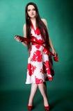 Giovane donna in vestito fiorito da estate su verde Fotografia Stock