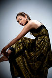 Giovane donna in vestito floreale dorato Fotografia Stock