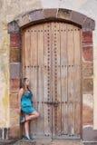 Giovane donna in vestito lungo che sta nella parte anteriore una vecchia porta fuoco Fotografia Stock Libera da Diritti