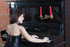Giovane donna in vestito nero che gioca il piano Fotografia Stock Libera da Diritti