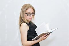 Giovane donna in vestito nero con i vetri che legge un libro Immagine Stock Libera da Diritti