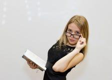 Giovane donna in vestito nero con i vetri che legge un libro Immagini Stock Libere da Diritti