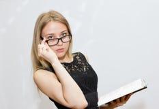 Giovane donna in vestito nero con i vetri che legge un libro Fotografia Stock