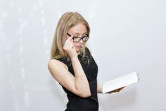Giovane donna in vestito nero con i vetri che legge un libro Fotografia Stock Libera da Diritti