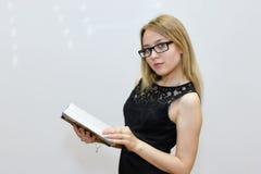 Giovane donna in vestito nero con i vetri che legge un libro Immagini Stock