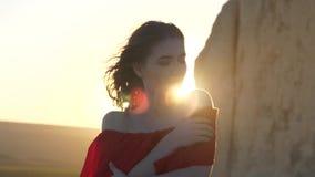 Giovane donna in vestito rosso con gli sguardi al sole che nascondendosi dietro la scogliera il vento scuote i suoi capelli stock footage