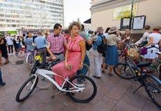 Giovane donna in vestito rosso sulla bicicletta d'annata nell'inizio aspettante della folla di retro crociera di festival immagini stock libere da diritti