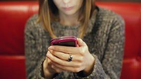 Giovane donna in vetri che mandano un sms su uno smartphone video d archivio