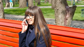Giovane donna in vetri che parla sul telefono modile in un parco della città stock footage