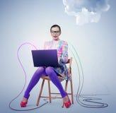 Giovane donna in vetri che si siedono su una sedia con un computer portatile Computazione della nuvola di concetto Fotografie Stock Libere da Diritti