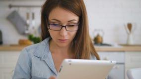 Giovane donna in vetri e camicia blu che lavorano alla sua compressa con la cucina stock footage