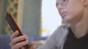 Giovane donna in vetri, sedentesi in un caffè asiatico, facendo uso di Internet in uno smartphone video d archivio